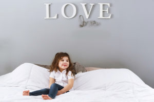 toddler girl with white shirt and jeans on bed photographed by boston photographer nicole loeb