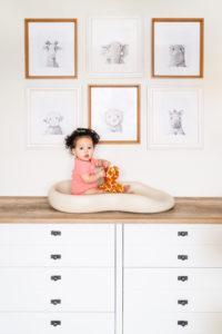 baby girl sitting with giraffe stuffed animal on dresser photographed by boston photographer nicole loeb