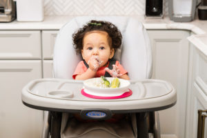 baby girl with cottage cheese in highchair photographed by boston photographer nicole loeb