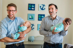 two fathers with newborn baby boy twins in nursery photographed by boston photographer nicole loeb