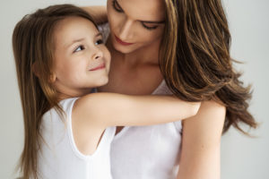 mother with toddler girl in white shirts on white seamless photographed by boston photographer nicole loeb