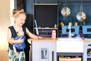 toddler with play kitchen and doll photographed by boston photographer nicole loeb
