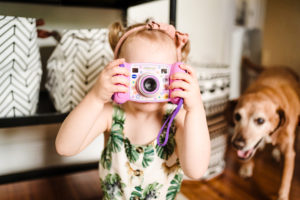 toddler girl with camera and dog photographed by boston photographer nicole loeb