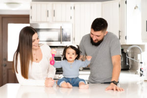 baby girl with parents in the kitchen photographed by boston photographer nicole loeb