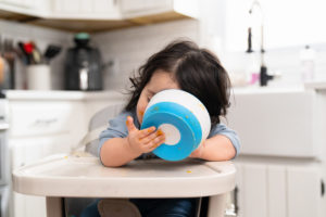 asian baby girl with baby food bowl in highchair photographed by boston photographer nicole loeb