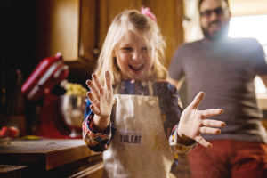 girl making chocolate chip cookies with family in kitchen photographed by boston photographer nicole loeb