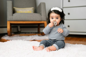 baby girl with bibs pacifier in nursery photographed by boston photographer nicole loeb