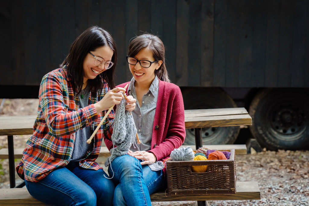 asian woman knitting at campfire at getaway house photographed by outdoor photographer nicole loeb