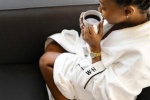 black woman enjoying coffee in Whitney hotel robe in hotel room photographed by Boston Photographer Nicole Loeb