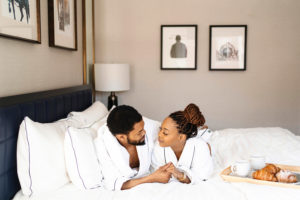 black couple enjoying breakfast in bed in Whitney hotel robe in hotel room photographed by Boston Photographer Nicole Loeb