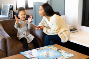 black mother and daughter playing board game photographed by Boston photographer Nicole Loeb