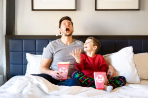 father and son eating popcorn in bed in a hotel room photographed by Boston photographer Nicole Loeb