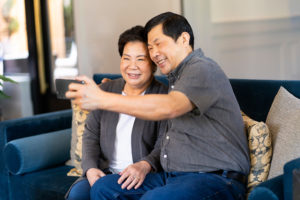 older asian senior couple taking selfie together on a couch photographed by Boston photographer Nicole Loeb