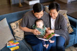 older asian senior couple reading books with grandson on a couch photographed by Boston photographer Nicole Loeb
